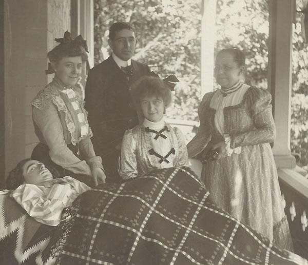Will Adams with his parents Sidney and Harriet Adams, sister Bertha, and friend Norma Ross (seated) on the Adams Family Porch. (Photo Courtesy of the J.M. Longyear Research Library)